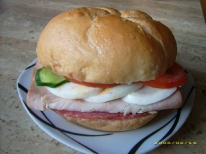 Kaiser roll with turkey salami egg tomato and cucumber